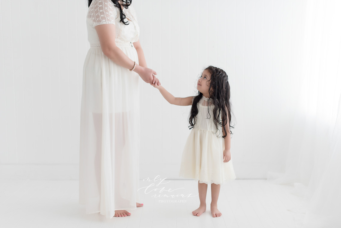 little girl looking up at her mom at photography studio in Pearland