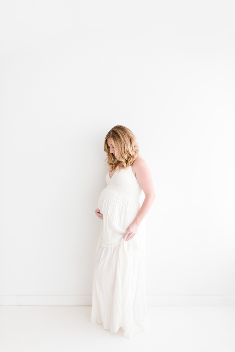 pregnant mom standing agains the wall holding her bump and dress