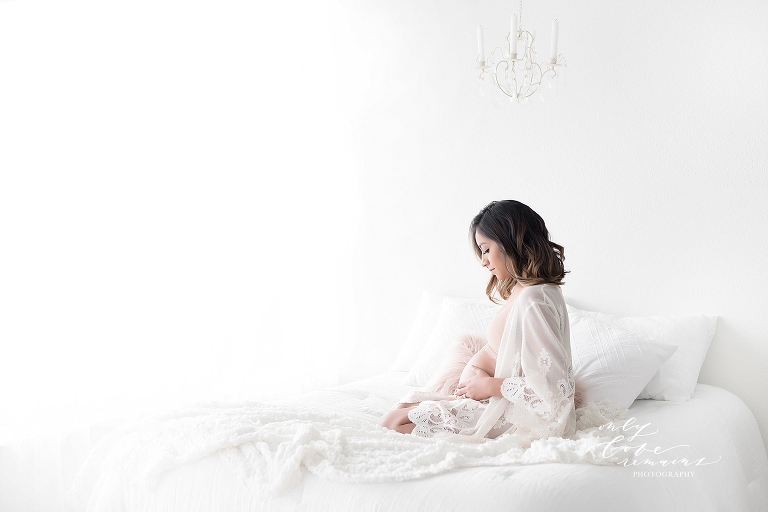 beautiful mom sitting on a bed holding her baby